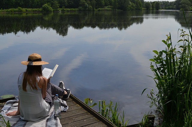 Woman sitting on dock reading