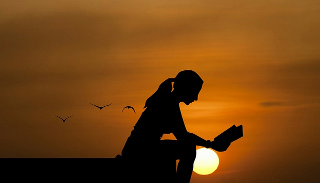 Silhouette of girl reading book against orange sky